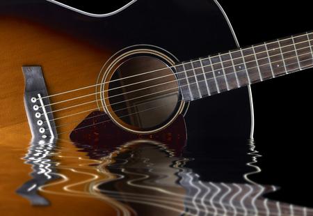 guitarra acustica: detalle de una guitarra ac�stica en la superficie del agua en la parte trasera reflectante negro Foto de archivo
