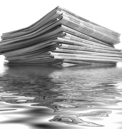 partly sunken stack of newspapers on reflective water surface Stock Photo