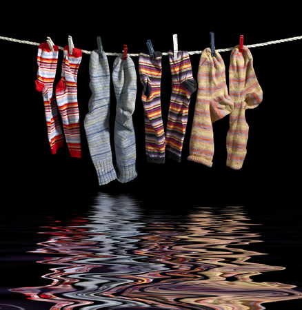 clothesline with some multicolored sox fixed with clothes pins over reflective water surface in black back