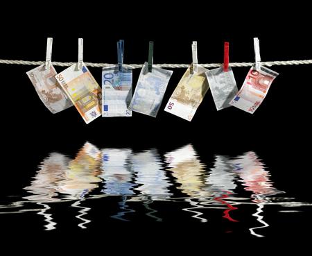 moistness: clothesline con alcune banconote in euro fissati con mollette sulla superficie dell'acqua riflettente in nero