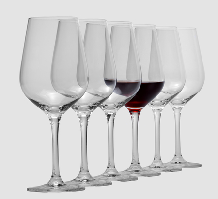 consecutive: some wine glasses standing consecutive in a row in light grey back, one partly filled with red wine