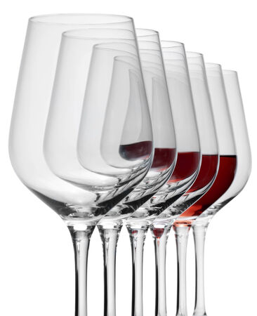 consecutive: some wine glasses standing consecutive in a row in white back, one partly filled with red wine Stock Photo