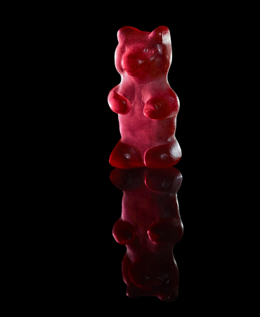 red translucent gummy bear in black reflective back Stock Photo