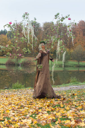 riparian: autumn scenery including a adapted fairy dressed performing female actor
