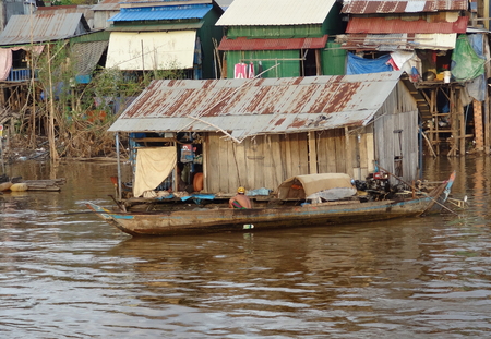 riparian: riparian scenery with house and boat at a river in Cambodia Stock Photo