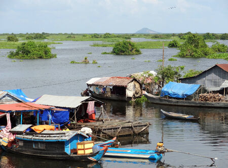 pile dwelling: waterside scenery with rural houses and boats at the Tonle Sap, a river in Cambodia