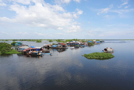 riparian: waterside scenery with rural houses and boats at the Tonle Sap, a river in Cambodia