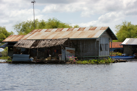 pile dwelling: waterside scenery with rural house at the Tonle Sap, a river in Cambodia