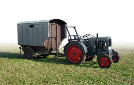 traction: historic traction engine with rundown trailer on a meadow, gradient isolated