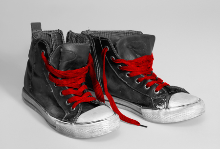 accouterment: pair of rundown sneakers with red shoelaces Stock Photo