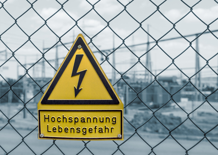 transformator: yellow german high voltage warning sign on a mesh wire fence in front of a blue toned electrical substation in Southern Germany