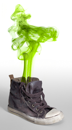 symbolic: rundown sneaker with symbolic green smoke cloud Stock Photo