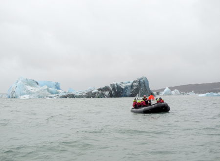 wavily: coastal scenery with iceberg and rubber boat seen in Iceland