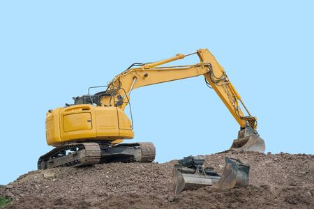 tracked: yellow digger on earth pile in front of blue back Stock Photo