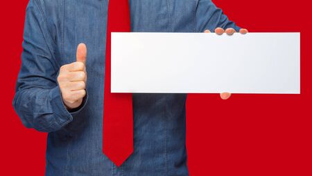 commercialization: male person holding a white blank sign in red back