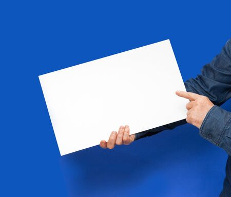 commercialization: male person holding a white blank sign in blue back