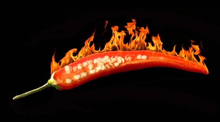 flamy: studio shot of a sliced burning red chili in dark back