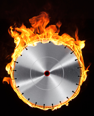 cut off saw: frontal shot of a diamond studded burning cutting wheel in black back