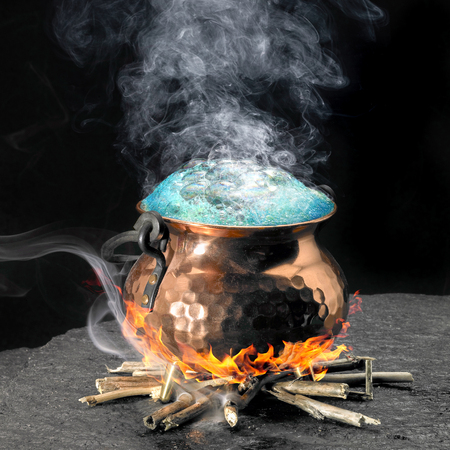 magical equipment: spumous potion and copper cauldron on a fireplace