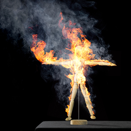 flamy: a burning wooden artist doll standing on a desktop in black back,