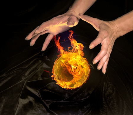 magical equipment: high angle shot of a burning crystal ball surrounded by black crinkly fabrics and two hands around