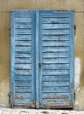 rundown: detail of a old rundown blue wooden door with blue flaking paint