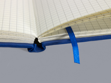 bookmark: a open blue notebook with graph paper detail and bookmark in grey back