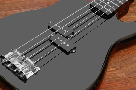 reflectance: detail of a black bass guitar in brown wooden back Stock Photo