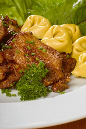repast: roasted chicken dish with fresh green salad and tortellini noodles on a white plate Stock Photo