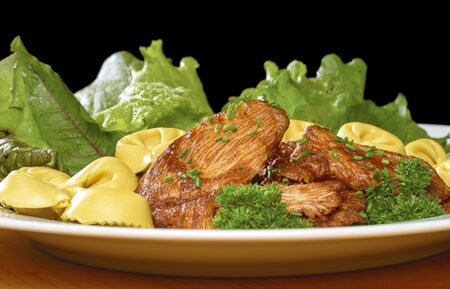 pullet: low angle shot of a roasted chicken dish with fresh green salad and tortellini noodles on a white plate in front of black back