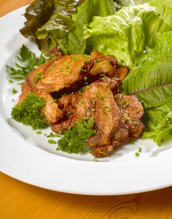 pullet: roasted chicken dish with fresh green salad on a white plate