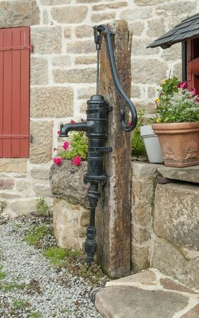 bomba de agua: black historic water pump seen in Brittany, France