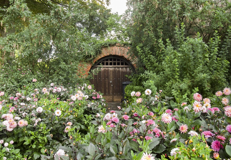 historic cellar entrance surrounded by flowers and other vegetation
