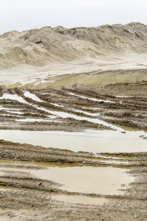skidmarks: wet scenery with skidmarks around a light brown heap of earth
