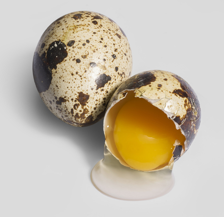 two brown dappled quail eggs with a opened one with egg white draining off