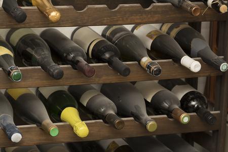 detail shot of dusty wine bottles in a wooden wine rack