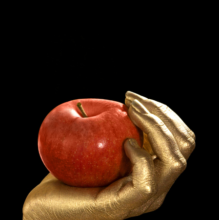 golden feminine hand holding a perfect red apple, Studio shot in black back Stock Photo