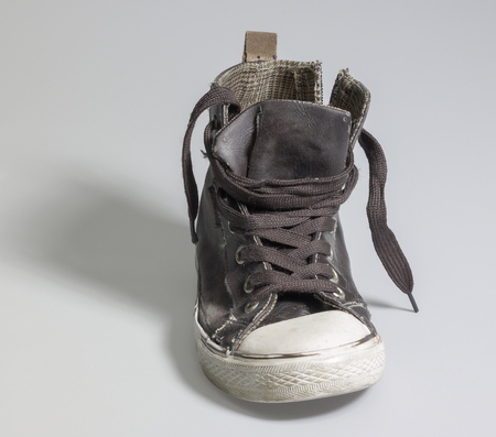 a old rundown brown sneaker in grey back
