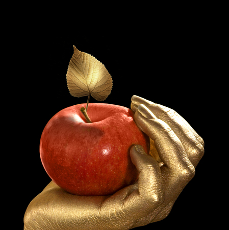 golden feminine hand holding a perfect red apple with golden leaf, Studio shot in black back
