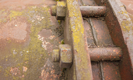 weathered rusty industrial closeup with old corroded appliance with screws