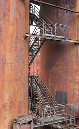 weathered rundown industrial scenery with old corroded steel girders, stairs and metal tubes Stock Photo