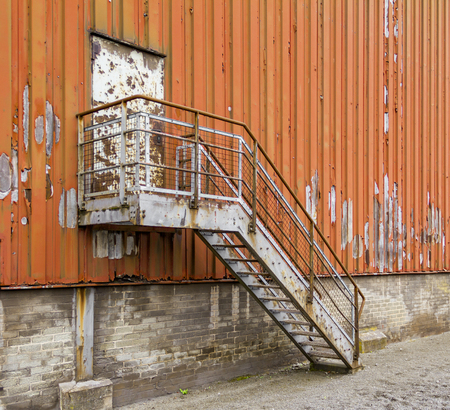 metallic stairs: weathered rundown industrial scenery with old corroded stairway and door