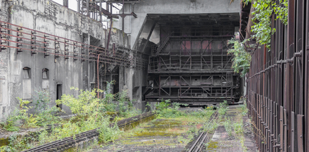 rotten industrial architectural scenery partly covered by vegetation