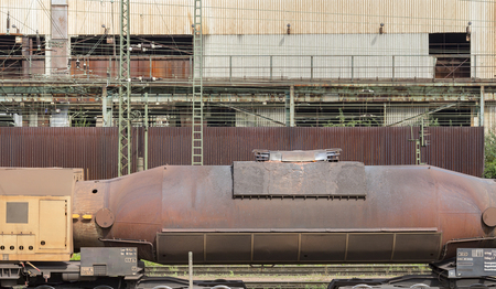 weathered rusty industrial scenery with old corroded torpedo car filled with molten pig iron
