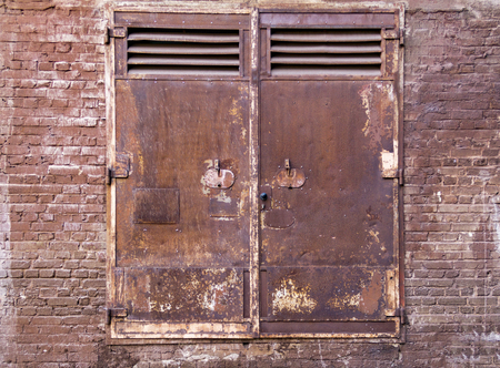 weathered rusty industrial scenery with old corroded metallic doors and dirty brick wall Stock Photo