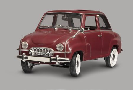 Model of a historic red micro car in grey back Фото со стока