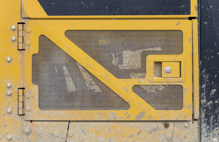 dirty yellow engine cover grill of a construction machine