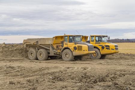 Camiones volquete en un sitio de construcción arcilloso Foto de archivo