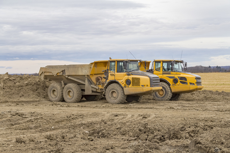 dump trucks at a loamy construction site Stock Photo
