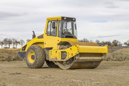 yellow road roller at a loamy construction site Stock Photo